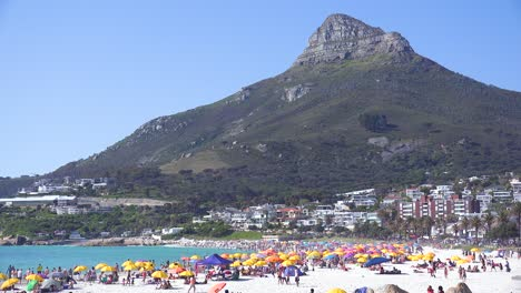Establishing-shot-of-a-beautiful-busy-holiday-beach-scene-at-Camps-Bay-Cape-Town-South-Africa-with-Lions-Head-peak-background-2