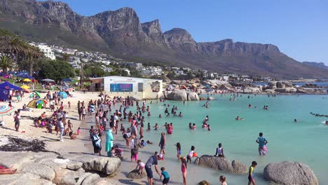 A-crowded-and-busy-holiday-beach-scene-at-Camps-Bay-Cape-Town-South-Africa-with-Twelve-Apostles-mountains-background