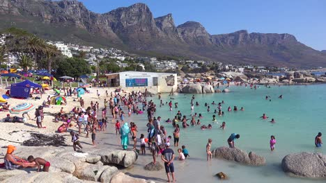 A-crowded-and-busy-holiday-beach-scene-at-Camps-Bay-Cape-Town-South-Africa-with-Twelve-Apostles-mountains-background-1