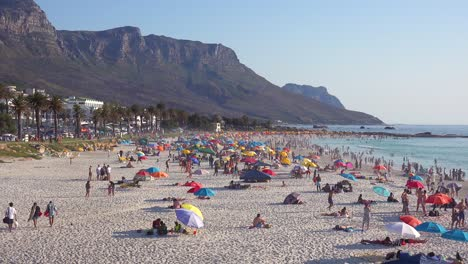 A-crowded-and-busy-holiday-beach-scene-at-Camps-Bay-Cape-Town-South-Africa-with-Twelve-Apostles-mountains-background-2
