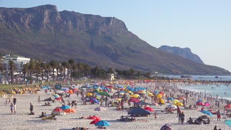 Eine-überfüllte-Und-Geschäftige-Urlaubsstrandszene-In-Camps-Bay-Kapstadt-Südafrika-Mit-Zwölf-Apostelbergen-Im-Hintergrund-3