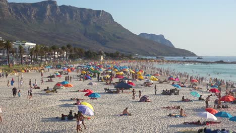 Spectacular-aerial-over-a-crowded-and-busy-holiday-beach-at-Camps-Bay-Cape-Town-South-Africa-with-Twelve-Apostles-mountains-background