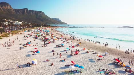 Spectacular-aerial-over-a-crowded-and-busy-holiday-beach-at-Camps-Bay-Cape-Town-South-Africa-with-Twelve-Apostles-mountains-background-1