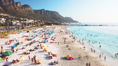 Spectacular-aerial-over-a-crowded-and-busy-holiday-beach-at-Camps-Bay-Cape-Town-South-Africa-with-Twelve-Apostles-mountains-background-2
