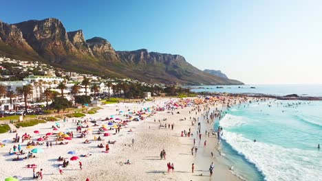 Spectacular-aerial-over-a-crowded-and-busy-holiday-beach-at-Camps-Bay-Cape-Town-South-Africa-with-Twelve-Apostles-mountains-background-3