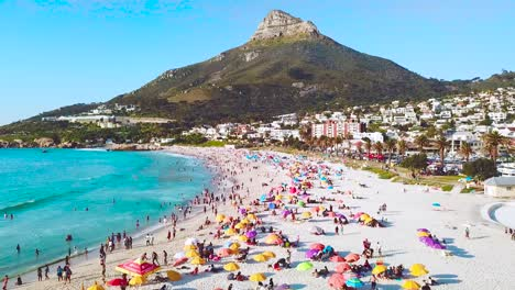 Spectacular-aerial-over-a-crowded-and-busy-holiday-beach-at-Camps-Bay-Cape-Town-South-Africa-with-Lion-s-Head-mountain-background