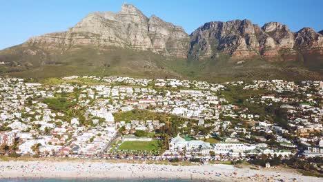 Luftbewegung-Entlang-Der-Reichen-Küste-Und-Eleganten-Häusern-Von-Camps-Bay-Kapstadt-Südafrika-Mit-Zwölf-Apostelbergen-Hintergrund