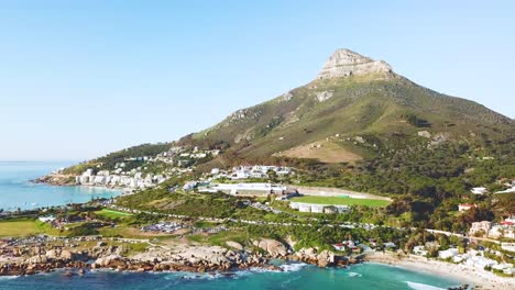 Aerial-moving-along-the-shoreline-of-Camps-Bay-Cape-Town-South-Africa-with-Lion-s-Head-mountain-background