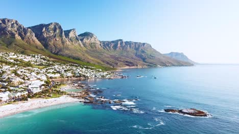 Aerial-moving-along-the-shoreline-of-Camps-Bay-Cape-Town-South-Africa-with-Twelve-Apostles-mountains-background