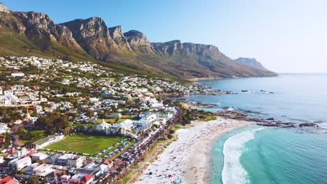 Aerial-moving-along-the-shoreline-of-Camps-Bay-Cape-Town-South-Africa-with-Twelve-Apostles-mountains-background-1