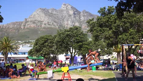 Kids-play-on-a-teeter-totter-on-a-playground-at-Camps-Bay-Cape-Town-South-Africa-with-Table-Mountain-background