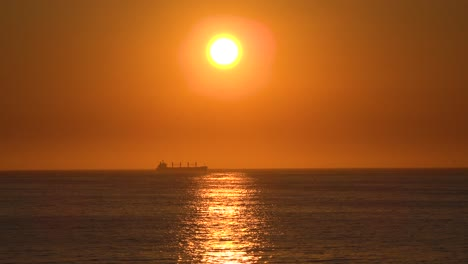 A-distant-container-cargo-ship-or-tanker-travels-against-the-setting-sun-at-sunset