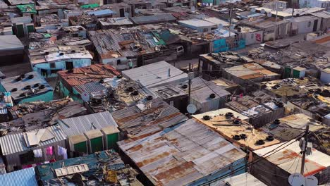 Aerial-over-ramshackle-tin-roofs-of-Gugulethu-one-of-the-poverty-stricken-slums-ghetto-or-townships-of-South-Africa