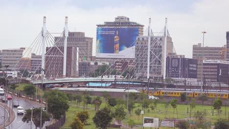 Toma-De-Establecimiento-De-Johannesburgo-Sudáfrica-Con-El-Puente-Nelson-Mandela-Y-El-Tren-De-Pasajeros-En-Primer-Plano