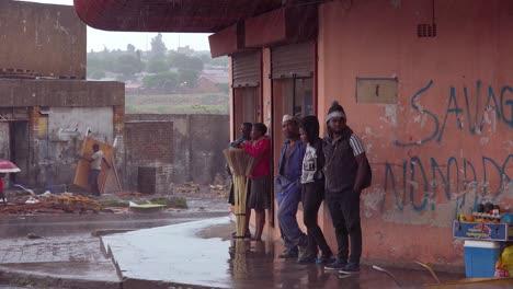 La-Gente-Espera-Bajo-La-Lluvia-En-La-Esquina-De-Una-Calle-En-El-Municipio-De-Soweto-Sudáfrica