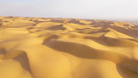 Astonishing-aerial-shot-over-the-vast-sand-dunes-of-the-Namib-Desert-ends-at-a-safari-van-and-people
