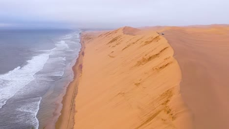 Astonishing-aerial-shot-over-the-vast-sand-dunes-of-the-Namib-Desert-along-the-Skeleton-Coast-of-Namibia-ends-on-safari-van-1