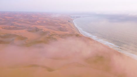 Good-high-aerial-shot-through-clouds-and-fog-over-the-vast-sand-dunes-of-the-Namib-Desert-along-the-Skeleton-Coast-of-Namibia