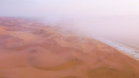 Good-high-aerial-shot-through-clouds-and-fog-over-the-vast-sand-dunes-of-the-Namib-Desert-along-the-Skeleton-Coast-of-Namibia-1