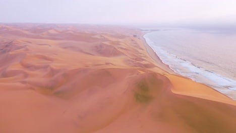 High-aerial-shot-through-clouds-and-fog-over-the-vast-sand-dunes-of-the-Namib-Desert-along-the-Skeleton-Coast-of-Namibia