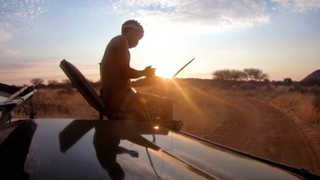 A-native-spotter-guide-sits-on-the-front-of-a-safari-jeep-vehicle-spotting-wildlife-on-the-plains-of-Africa-at-sunset