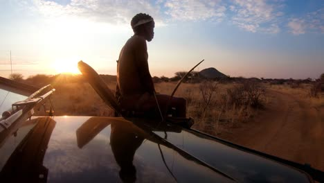 A-native-spotter-guide-sits-on-the-front-of-a-safari-jeep-vehicle-spotting-wildlife-on-the-plains-of-Africa-at-sunset-1