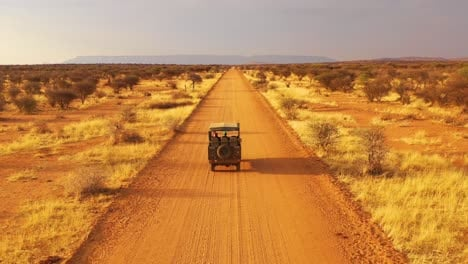 Aerial-of-a-safari-jeep-traveling-on-the-plains-of-Africa-at-Erindi-Game-Preserve-Namibia-with-native-San-tribal-spotter-guide-sitting-on-front-spotting-wildlife