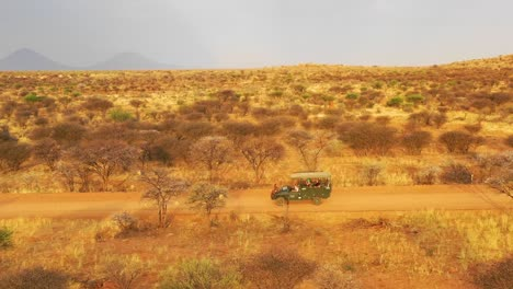 Aerial-of-a-safari-jeep-traveling-on-the-plains-of-Africa-at-Erindi-Game-Preserve-Namibia-with-native-San-tribal-spotter-guide-sitting-on-front-spotting-wildlife-1