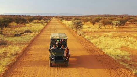 Antenne-Eines-Safari-Jeeps-Der-Auf-Den-Ebenen-Afrikas-Im-Erindi-Wildreservat-In-Namibia-Reist-Mit-Einheimischem-San-Tribal-Spotter-Führer-Der-Auf-Der-Vorderseite-Sitzt-Und-Wildtiere-Beobachtet-2