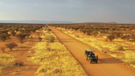 Aerial-of-a-safari-jeep-traveling-on-the-plains-of-Africa-at-Erindi-Game-Preserve-Namibia-with-native-San-tribal-spotter-guide-sitting-on-front-spotting-wildlife-3