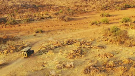 Aerial-of-a-safari-jeep-traveling-on-the-plains-of-Africa-at-Erindi-Game-Preserve-Namibia-with-native-San-tribal-spotter-guide-sitting-on-front-spotting-wildlife-4