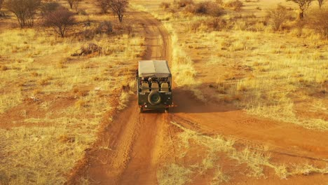 Aerial-of-a-safari-jeep-traveling-on-the-plains-of-Africa-at-Erindi-Game-Preserve-Namibia-with-native-San-tribal-spotter-guide-sitting-on-front-spotting-wildlife-5