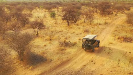 Vista-Aérea-of-a-safari-jeep-traveling-on-the-plains-of-Africa-at-Erindi-Game-Preserve-Namibia-with-native-San-tribal-spotter-guide-sitting-on-front-spotting-wildlife-6