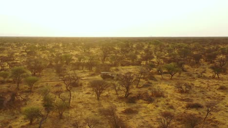 Excellent-aerial-of-a-safari-jeep-traveling-on-the-plains-of-Africa-at-Erindi-Game-Preserve-Namibia-with-native-San-tribal-spotter-guide-sitting-on-front-spotting-wildlife-1