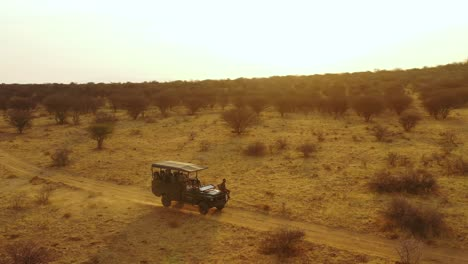 Aerial-of-a-safari-jeep-traveling-on-the-plains-of-Africa-at-Erindi-Game-Preserve-Namibia-with-native-San-tribal-spotter-guide-sitting-on-front-spotting-wildlife-8
