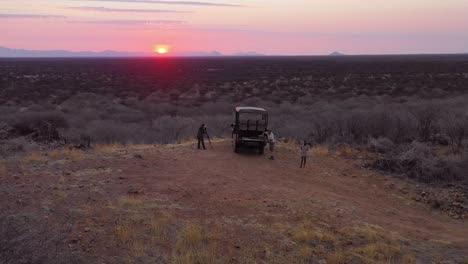 Aerial-of-tourists-enjoying-a-sunset-on-a-safari-jeep-at-the-vast-and-beautiful-Erindi-Game-Preserve-Namibia