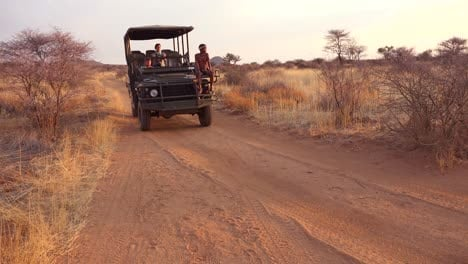 A-safari-jeep-passes-by-at-sunset-on-the-plains-of-Africa-Erindi-Park-Namibia-with-native-tribal-spotter-riding-on-front