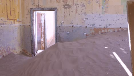 Sand-blows-through-an-abandoned-building-in-the-gem-mining-ghost-town-of-Kolmanskop-Namibia-1
