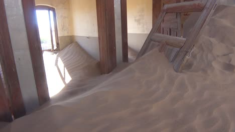 Sand-blows-through-an-abandoned-building-in-the-gem-mining-ghost-town-of-Kolmanskop-Namibia-4