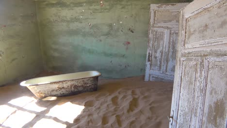 Sand-and-a-bath-tub-fills-an-abandoned-building-in-the-gem-mining-ghost-town-of-Kolmanskop-Namibia