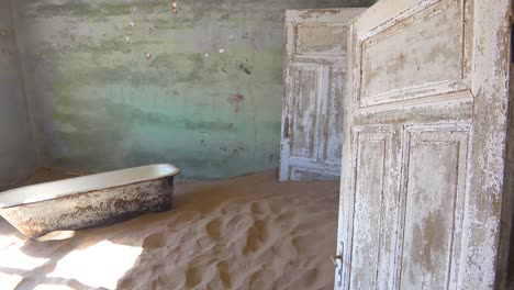 Sand-and-a-bath-tub-fills-an-abandoned-building-in-the-gem-mining-ghost-town-of-Kolmanskop-Namibia-1