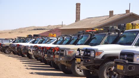 Dozens-of-safari-jeep-vehicles-parked-in-a-row-at-a-popular-desert-attraction-in-Namibia