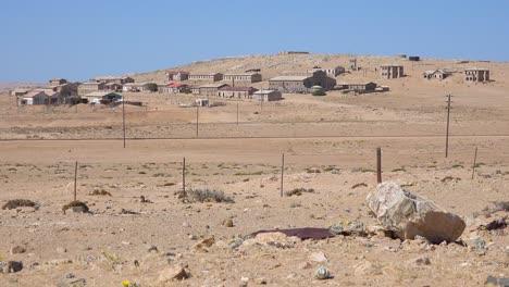 Exterior-establishing-shot-of-abandoned-buildings-in-the-Namib-desert-at-the-ghost-town-of-Kolmanskop-Namibia-1