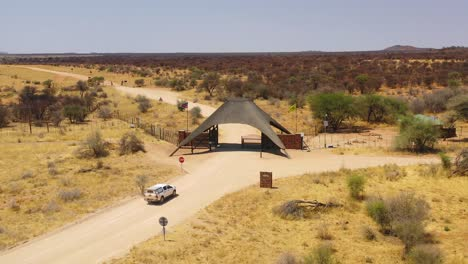 Vista-Aérea-of-a-safari-truck-or-vehicle-arriving-at-the-main-gate-of-the-Erindi-Reserve-or-fenced-wildlife-park-Namibia