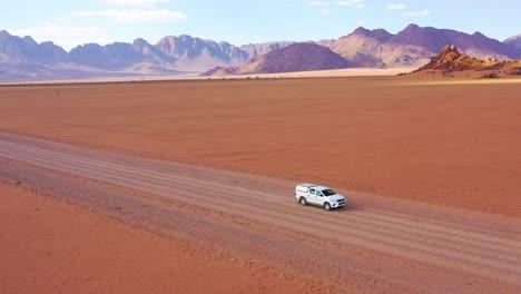 High-aerial-over-a-Toyota-safari-vehicle-heading-across-the-flat-barren-Namib-Desert-in-Namibia