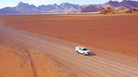 High-aerial-over-a-Toyota-safari-vehicle-heading-across-the-flat-barren-Namib-Desert-in-Namibia-1