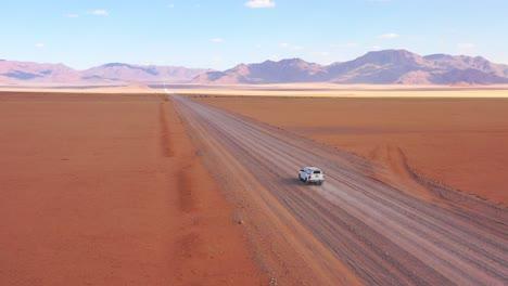High-aerial-over-a-Toyota-safari-vehicle-heading-across-the-flat-barren-Namib-Desert-in-Namibia-2