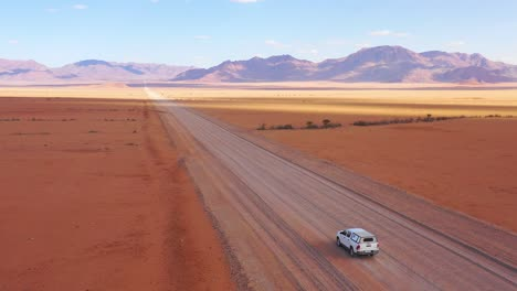 High-vista-aérea-over-a-Toyota-safari-vehicle-heading-across-the-flat-barren-Namib-Desert-in-Namibia-3