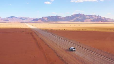 High-vista-aérea-over-a-Toyota-safari-vehicle-heading-across-the-flat-barren-Namib-Desert-in-Namibia-4