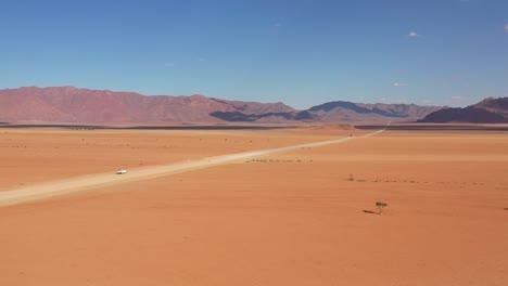 High-vista-aérea-over-a-Toyota-safari-vehicle-heading-across-the-flat-barren-Namib-Desert-in-Namibia-5